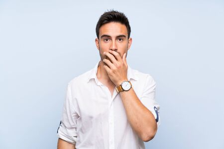 Handsome young man over isolated blue background surprised and shocked while looking right