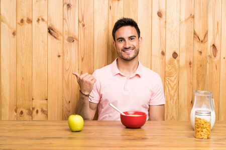 Handsome young man in a kitchen having breakfast pointing to the side to present a product