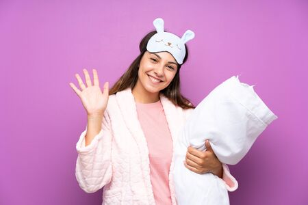 Young woman in pajamas and dressing gown over isolated purple background saluting with hand with happy expression Stockfoto