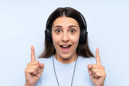 Young woman listening music over isolated blue background pointing up a great idea