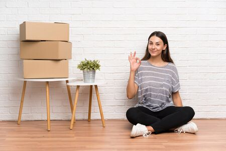 Young woman moving in new home among boxes showing an ok sign with fingers