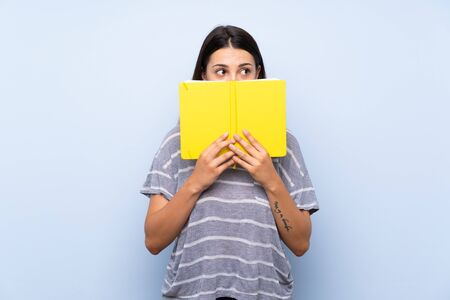 Young brunette woman over isolated blue background holding and reading a book