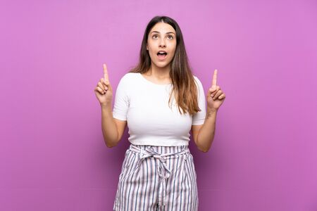 Young woman over isolated purple background surprised and pointing up Stockfoto