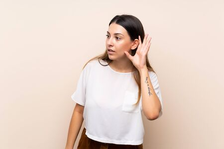 Young brunette woman over isolated background listening to something by putting hand on the ear Stockfoto