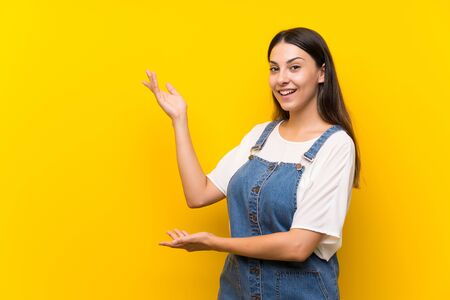 Young woman in dungarees over isolated yellow background extending hands to the side for inviting to come