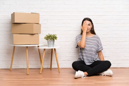 Young woman moving in new home among boxes covering a eye by hand