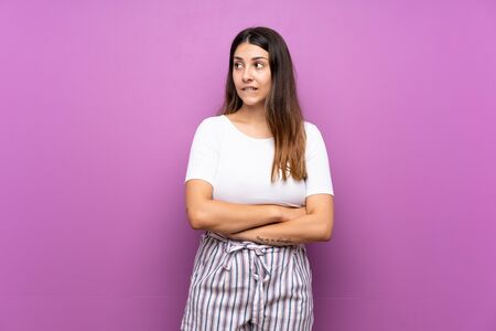 Young woman over isolated purple background with confuse face expression Фото со стока