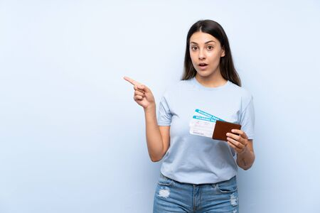 Traveler woman with boarding pass over isolated blue wall surprised and pointing side
