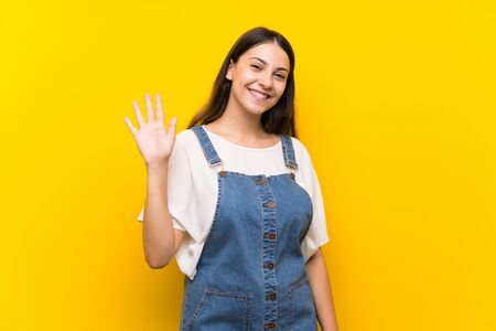Young woman in dungarees over isolated yellow background saluting with hand with happy expression