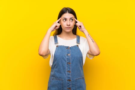 Young woman in dungarees over isolated yellow background having doubts and thinking