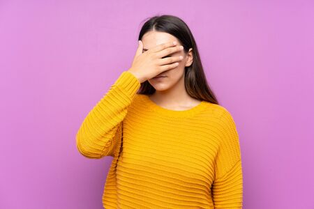 Young woman over isolated purple background covering eyes by hands Stockfoto