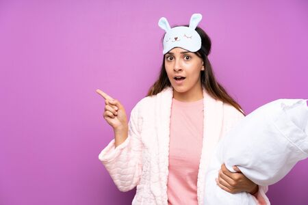 Young woman in pajamas and dressing gown over isolated purple background surprised and pointing side