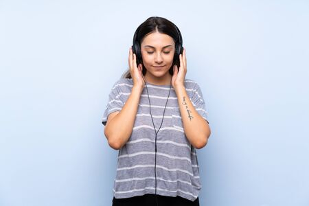 Young brunette woman over isolated blue background listening to music with headphones Stock Photo