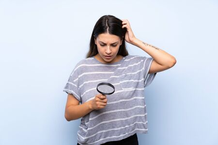 Young brunette woman over isolated blue background holding a magnifying glass
