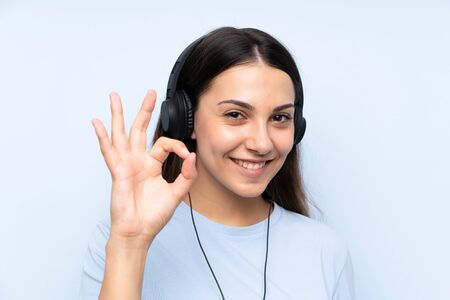 Young woman listening music over isolated blue background showing ok sign with fingers Stock Photo