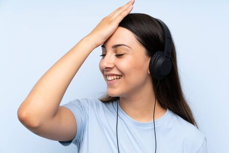 Young woman listening music over isolated blue background has realized something and intending the solution