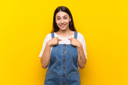 Young woman in dungarees over isolated yellow background with surprise facial expression Stock fotó