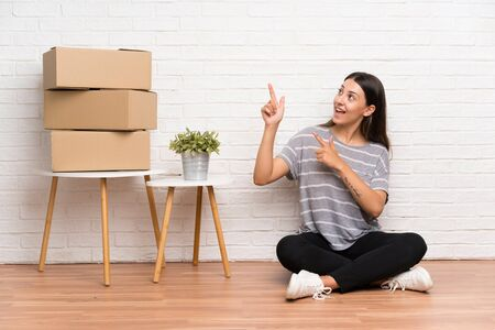 Young woman moving in new home among boxes pointing with the index finger a great idea Standard-Bild - 132057902
