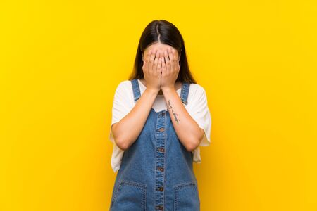 Young woman in dungarees over isolated yellow background with tired and sick expression