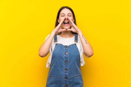 Young woman in dungarees over isolated yellow background shouting and announcing something