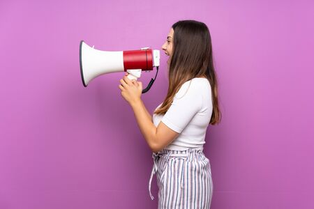 Young woman over isolated purple background shouting through a megaphone Stockfoto