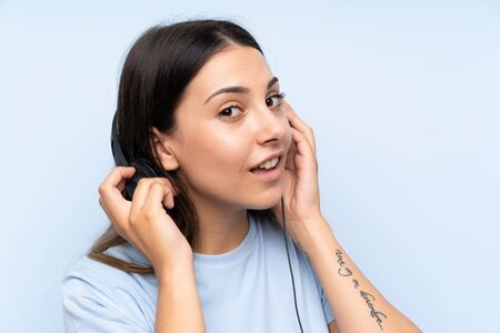Young woman listening music over isolated blue background