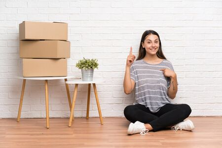 Young woman moving in new home among boxes with surprise facial expression Stock fotó