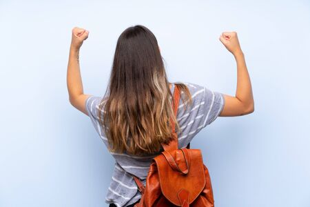 Young brunette woman over isolated blue background with backpack