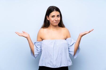 Young brunette woman over isolated blue background having doubts with confuse face expression Фото со стока