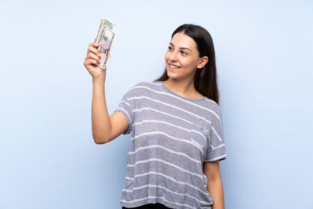Young brunette woman over isolated blue background taking a lot of money