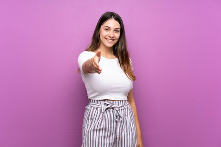 Young woman over isolated purple background shaking hands for closing a good deal