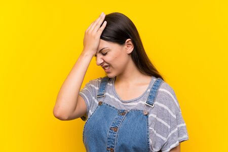 Young woman in dungarees over isolated yellow background having doubts with confuse face expression Фото со стока