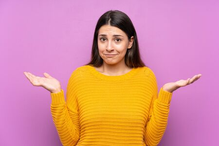 Young woman over isolated purple background having doubts with confuse face expression