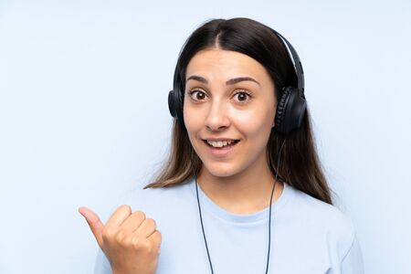 Young woman listening music over isolated blue background pointing to the side to present a product