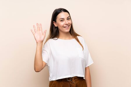Young brunette woman over isolated background saluting with hand with happy expression