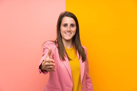 Young woman with pink suit over colorful background handshaking after good deal