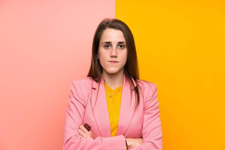 Young woman with pink suit over colorful background keeping arms crossed Stock Photo