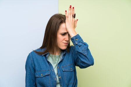 Young woman over colorful background having doubts with confuse face expression