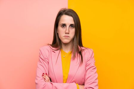 Young woman with pink suit over colorful background sad