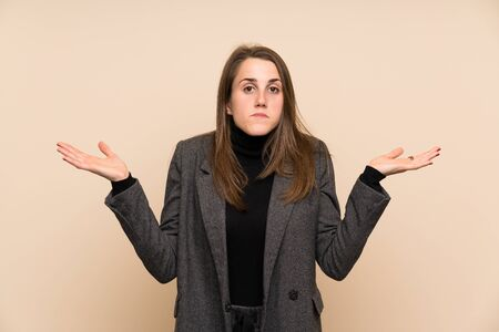 Young woman over isolated wall having doubts with confuse face expression