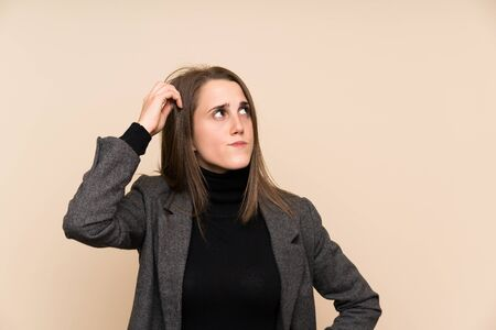 Young woman over isolated wall having doubts and with confuse face expression Фото со стока