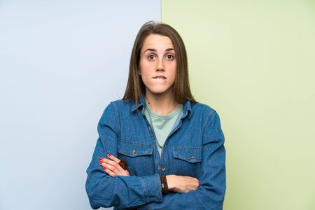 Young woman over colorful background having doubts and with confuse face expression