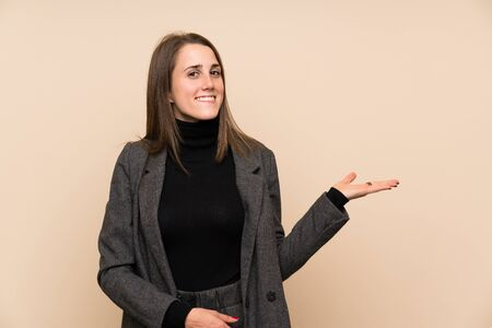 Young woman over isolated wall extending hands to the side for inviting to come Standard-Bild