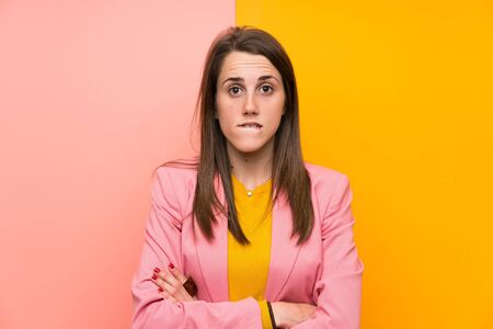 Young woman with pink suit over colorful background having doubts and with confuse face expression Фото со стока