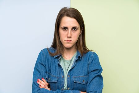 Young woman over colorful background sad