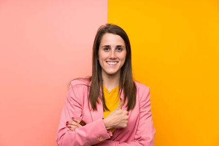 Young woman with pink suit over colorful background giving a thumbs up gesture