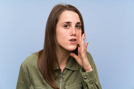 Young woman over isolated blue wall whispering something Standard-Bild