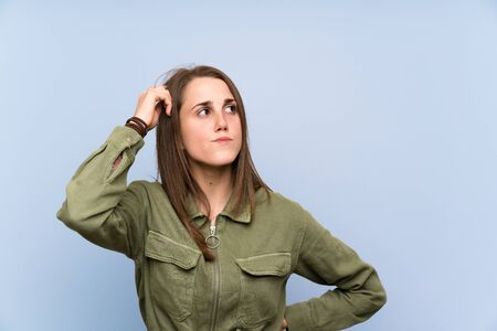 Young woman over isolated blue wall having doubts and with confuse face expression Фото со стока