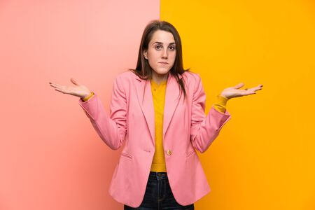 Young woman with pink suit over colorful background having doubts with confuse face expression