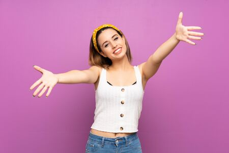 Pretty young woman over isolated purple wall presenting and inviting to come with hand